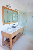 Washstand with twin undermount basins, framed mirror on wall and floor-level shower area with glass partition in modern bathroom