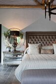 Double bed with button-tufted headboard and table lamp on bedside table below round mirror in elegant vintage bedroom