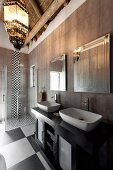 Elegant bathroom with chequered floor, washstand with twin sinks against grey-tiled wall and floor-level shower in background