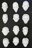 Various white theatre masks hung on black wall
