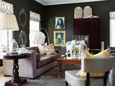 Lounge area with armchair, round, dark wood side table and table lamp next to sofa in black-painted living room