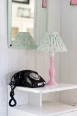 Black, vintage telephone and table lamp with pink base on small, white cabinet below wall-mounted mirror
