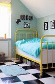 Yellow, vintage, metal-framed bed on chequered floor in teenager's attic bedroom