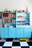 Dressers painted pale blue in child's bedroom with chequered floor