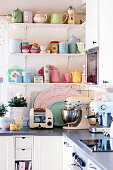 Pastel, retro crockery on shelving above kitchen counter
