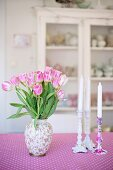 Vase of pink tulips and white candles in candlesticks on pink and white patterned tablecloth