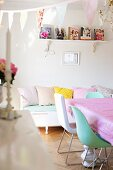Chairs at table in front of white bench with scatter cushions in feminine dining room