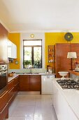 Open-plan kitchen with white island counter, wooden fitted cabinets and yellow-painted walls