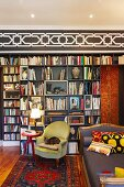 Antique, green armchair and Biedermeier-style sofa in front of modern bookcase below black and white stencilled frieze on wall