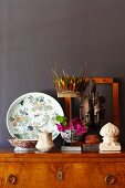 Antique collectors' items on antique cabinet against dark brown wall