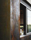 Corten steel facade of house with view of interior through sliding window