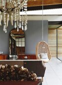 Sofa, wicker hanging chair and lattice full-length mirror in interior with tiled floor; chandelier and stacked firewood in foreground