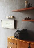 Old typewriter on retro sideboard below ornaments and artworks on wooden floating shelves on grey marbles wall