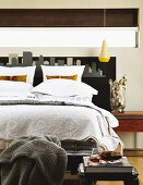 Stencilled skyline as decorative headboard of double bed below ribbon window and yellow pendant lamp