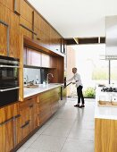 Woman opening oven in spacious designer kitchen with exotic wooden fronts