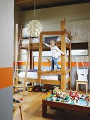 Boy climbing on bunk beds; orange dado stripe and branch structures painted on walls