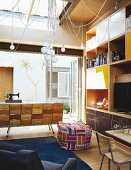 Vintage designer cabinet and colourful, patchwork pouffe in front of modular shelving with brightly coloured elements
