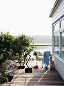 Holiday home with wooden deck with holes left for tree branches and view across lagoon landscape