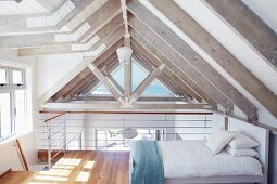 Guest bed on mezzanine below pale roof beams in modern holiday home