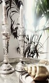 Two ornate silver candlesticks on tray behind snail shell ornament