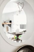 White pillar candle in silver candlestick decorating porthole aperture