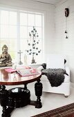 Round wooden table with turned legs painted black and white armchair in front of lattice windows in corner of wood-panelled room
