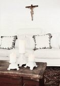 View across three candlesticks on wooden trunk to white sofa with scatter cushions