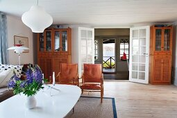 Vase of flowers on white, oval table and classic armchair in spacious living area in Swedish wooden house
