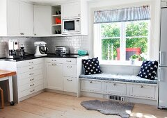 Corner unit in Swedish, country-house kitchen with blue and white accessories on integrated window seat
