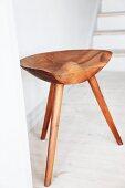 Three-legged wooden stool with ergonomic seat