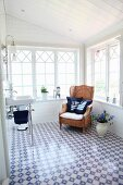 Sink and wicker armchair in conservatory-style extension with blue and white floor tiles and maritime scatter cushions