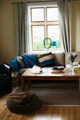 Wooden coffee table, sofa with striped scatter cushion and brown bean bag in front of window in rustic interior