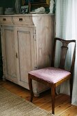 Antique wooden chair with seat upholstered in gingham next to pale wooden dresser