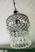 Vintage pendant lamp with glass pendants suspended from white wooden ceiling