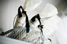 White bags tied with black ribbons in wire basket