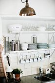 Crockery and glasses on white bracket shelves with cups hanging from row of hooks