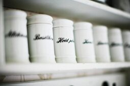 Labelled, white china spice jars on shelf
