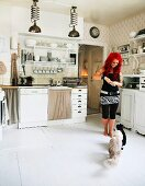 Woman with cats in white, rustic, country-house kitchen