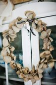 Hand-crafted wreath of leaves hung on door of glass-fronted cabinet