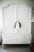 Antique, white-painted wardrobe on delicate feet with small fabric bag and wreath hanging from key