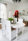 White, rustic dining area with loose-covered chairs and woman lighting candles