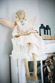 Angel doll sitting on cupboard