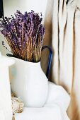 Bouquet of dried lavender in white, vintage metal jug
