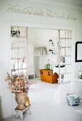 Fabric flowers in vase in antique Greek style in front of lattice partition with view into dining room