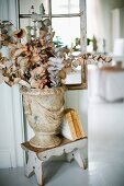 Branches of fabric leaves in vase in antique Greek style in front of lattice partition