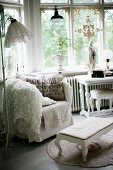 Comfortable armchair with scatter cushions and upholstered footstool in window bay