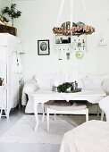 Wreath suspended from ceiling above coffee table with curved legs, stool and couch