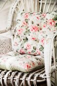 Nostalgic, floral cushions on white-painted rattan chair
