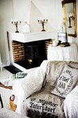 Armchair with lace blanket and printed linen throw in front of open fireplace in rustic interior