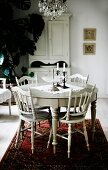Round dining table and chairs with turned legs painted white on red Oriental rug in rustic interior